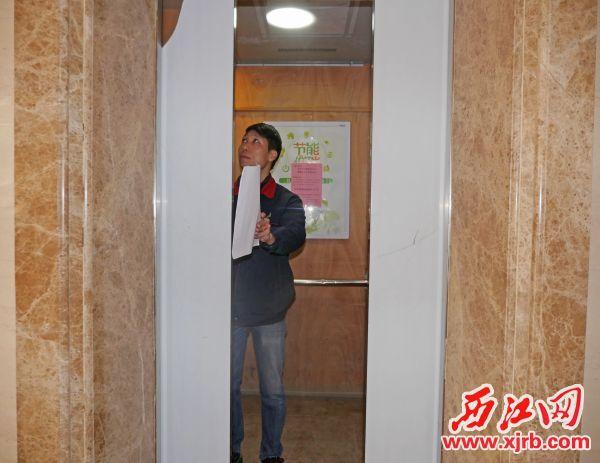 电梯管理员在检测电梯光幕。 西江日报记者 吴威豪 摄