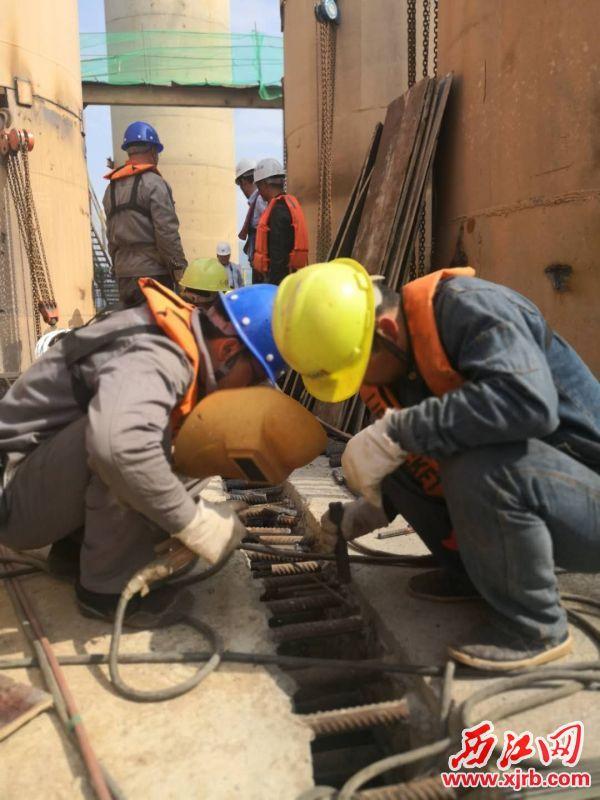 工人们正在焊接塔 基。 西江日报记者 肖桂芳 摄
