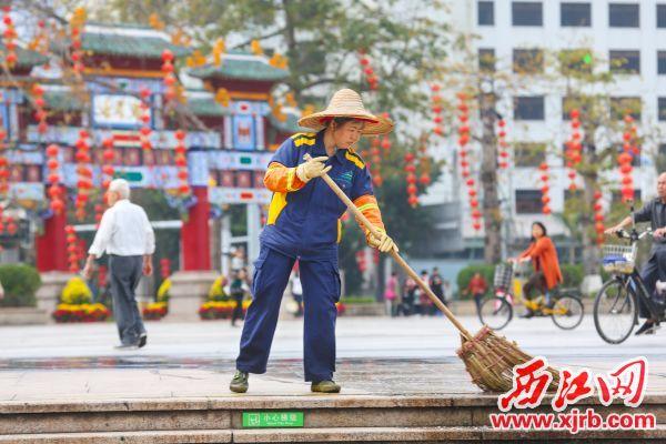 清洁工人在牌坊广场打扫卫生,让城市在节日里保持整洁。 西江日报记者 梁小明 摄