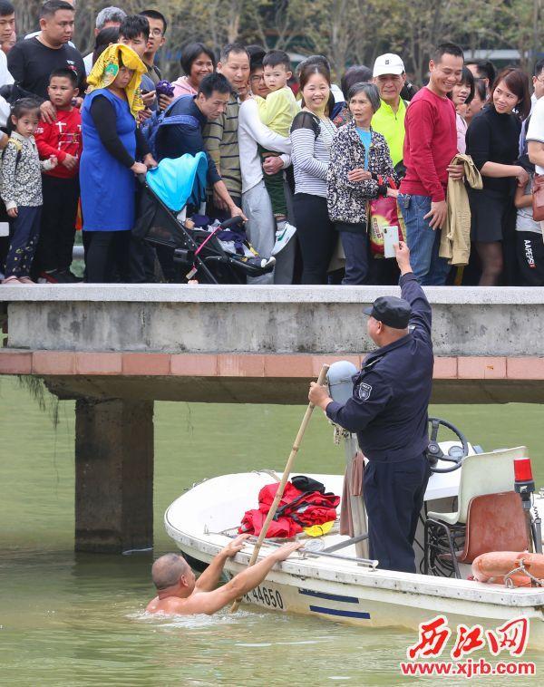 在七星岩桃花岛,肇庆渔政和水上搜救队工作人员为游客打捞掉进 湖里的手机。 西江日报记者 梁小明 摄
