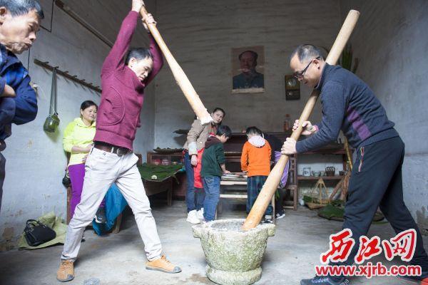 村民在用舂杵舂锤蒸熟的糯米。 广宁县供图