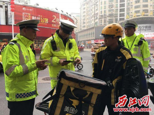 交警检查过往摩托车证件。 西江日报记者 杨丽娟 摄
