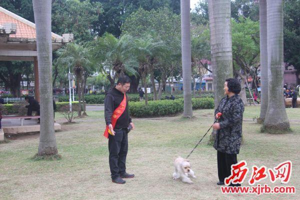 陈卫华(左)正劝导市民勿牵狗进入公园。 西江日报记者 严炯明 摄