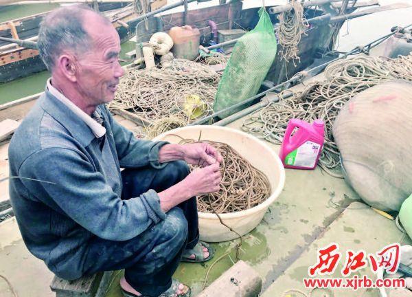 ▲渔民正在整理渔网、绳索等捕捞工具。 西江日报记者 谢江涛 摄