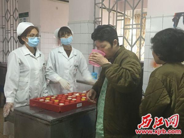 两名护士在给病人派药并监督她们服下。 西江日报记者 赖小琴 摄