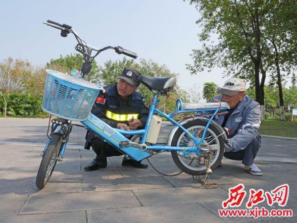 保安员邹木旺(左)正在为谢 伯修理掉了链子的电动车。 西江日报记者 吴威豪 摄