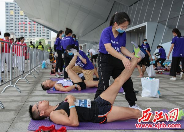 志愿者为赛后选手进行肌肉拉伸放松。 西江日报记者 梁小明 摄