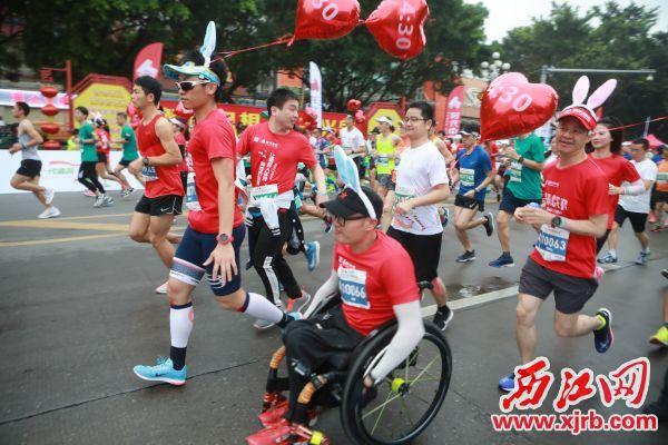 轮椅选手配速员张健奔跑在马拉松赛道上。 西江日报记者 刘春林 摄