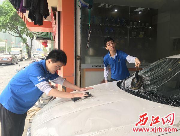 莫键(左)和李健诚在为客户洗车。 西江日报记者 潘粤华 摄