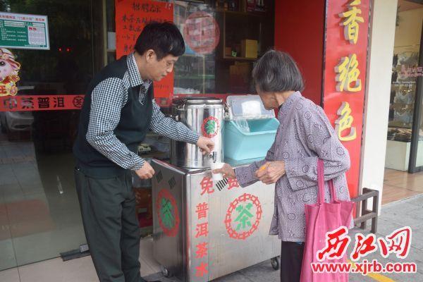 邱衛東(左)在店門口,為市民送上免費茶水。 西江日報記者 陳松連 攝
