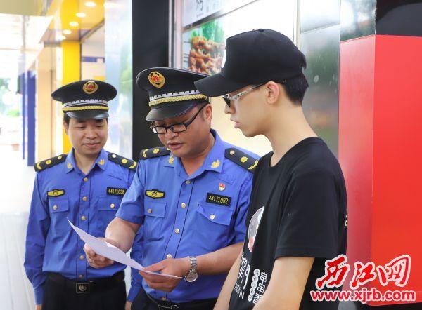 城管执法队员向市民宣传《烟头不落地,砚都更美丽》倡议书。 西江日报记者 严炯明 摄