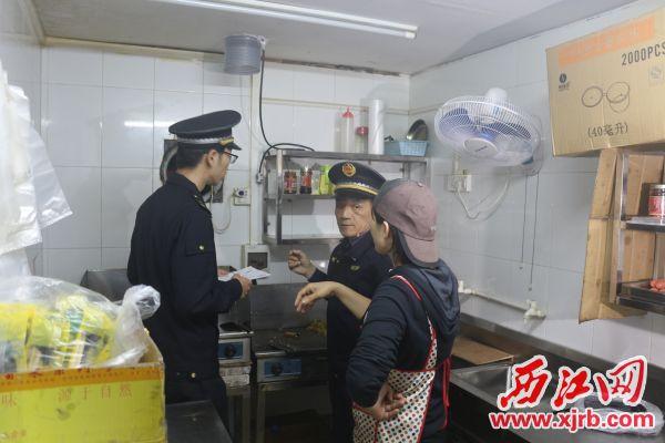 城管执法人员督促未完成油烟净化器安装的商户尽快完成安装。 西江日报记者 严炯明 摄