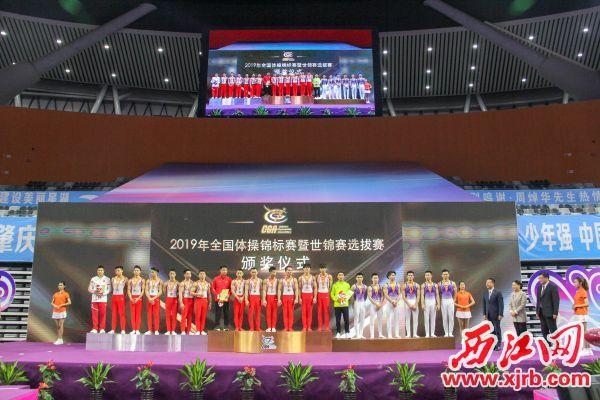 男子团体比赛前三名的队伍在领奖台上。  西江日报实习生 曹笑 摄