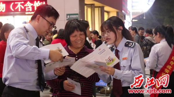 广宁县税务局青年志愿者细心地向市民讲解减税降费方面内容。 通讯员供图