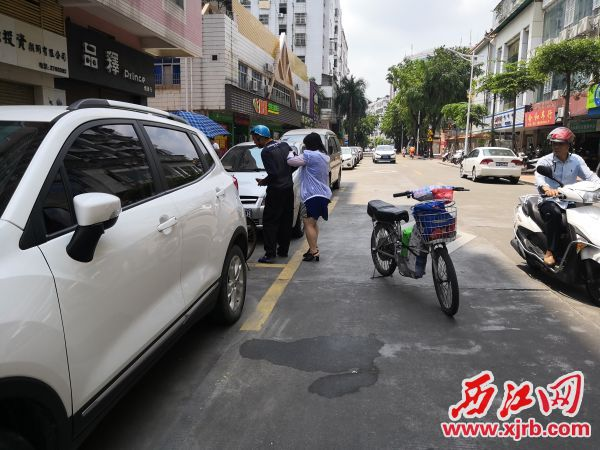 身穿白色防晒服的热心女士扶起跌倒的男子。 西江日报记者 陈松连 摄