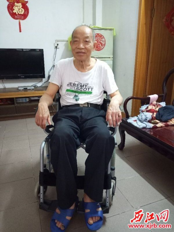 坐上新轮椅的黎汉能高兴地笑 了。 西江日报通讯员 摄