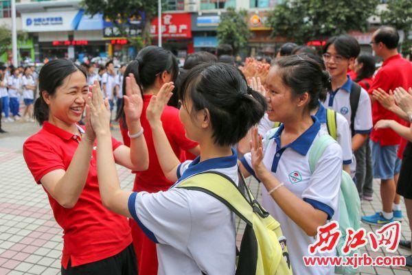 開考前老師與考生擊掌鼓勁。 西江日報記者 曹笑 攝