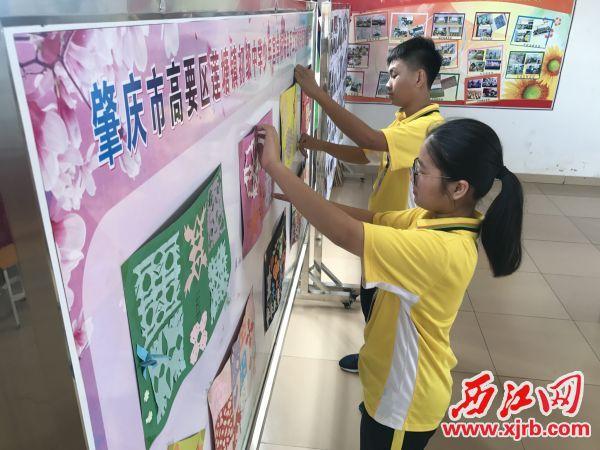 学生们正在张贴画报。 西江日报记者 夏紫怡 摄