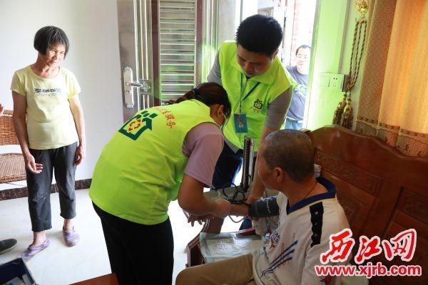 家庭医生团队成员正给签约对象量血压。 西江日报通讯员 江先荣 摄
