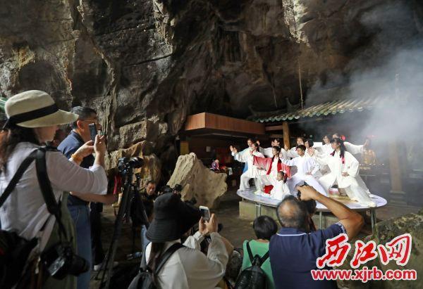 昨日,在七星岩出米洞,参加 表演的演员进行排练,吸引众多游客 围观。 西江日报记者 刘春林 摄