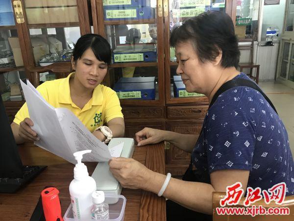 曾玲美(左)为居民讲解家庭医生服务内容。 西江日报记者 潘粤华 摄