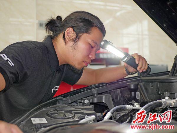 周健在檢查汽車發動機。 西江日報記者 吳威豪 攝