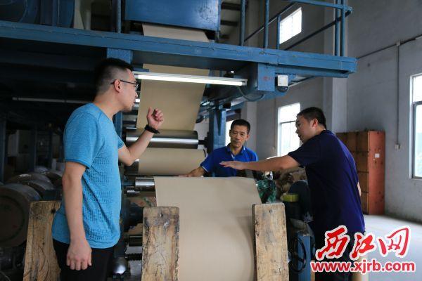 明珠纸业负责人(中)正介绍生产流程。 西江日报记者 杨丽娟 摄