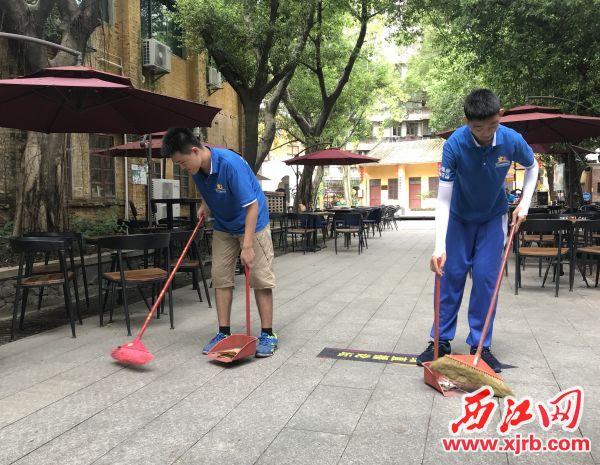 莫键(右)和李健诚在清扫路面。 西江日报记者 潘粤华 摄
