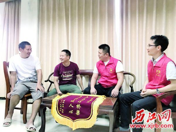苏贤军(左一)?#36864;?#36132;杰(左二)送来一面锦旗感谢救助站工作人员助其 家人团聚。 西江日报记者 夏紫怡 摄