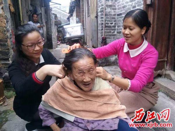 吴云红(左)正在帮老人剪头发。 受访者供图