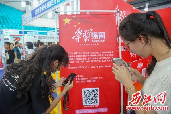 """南国书香节上市民们扫码下载""""学习强国APP""""。 西江日报记者 曹笑 摄"""