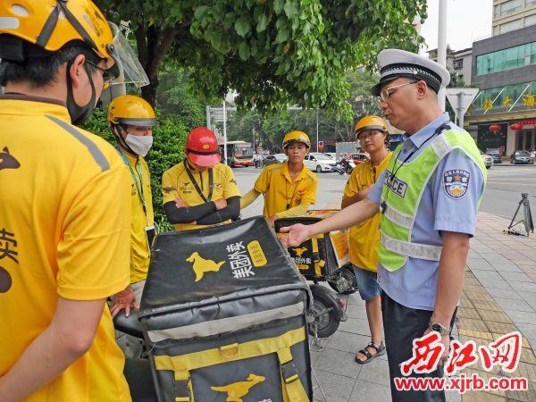 """交警对多名""""外卖小哥""""进行交通安全教育。 西江日报记者 吴威豪 摄"""