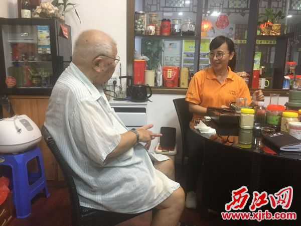 好心人龙伯(左)每月定期将善款交给李肇殷(右),由其帮自己捐助他人。 西江日报记者 赖小琴 摄