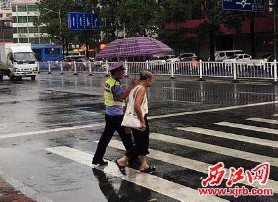 民警将市民送来的雨伞护送老 人过马路。 市民供图