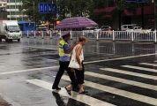 市民为值勤民警买伞遮风雨,民警撑伞护送老人过马路 一把雨伞传递出满满正能量
