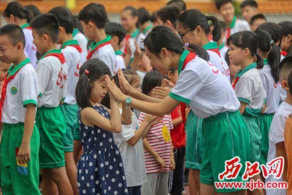 在肇庆市实验小学,高年级学生与羞涩的新生击掌,鼓励他们尽快融入。 西江日报记者 曹笑 摄