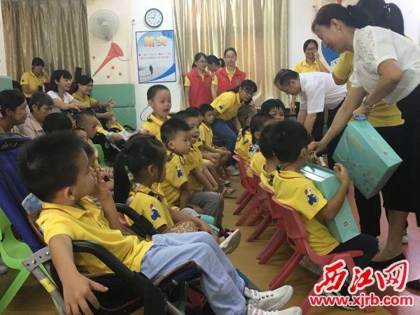 工作人员为孩子们派发月饼。 西江日报记者 赖小琴 摄