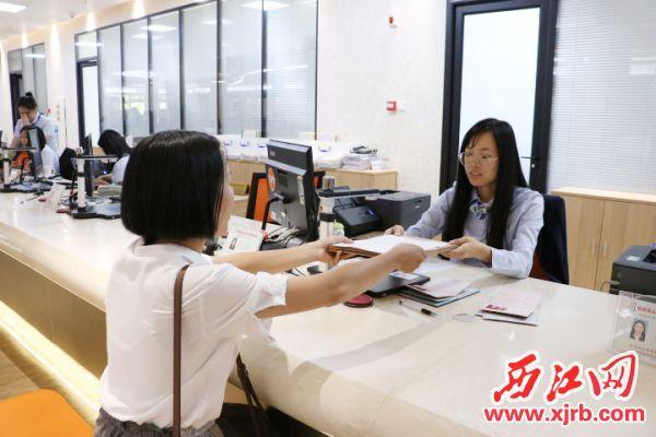 ▲房地产公司工作人员在服务窗口办理业务。 西江日报记者 甘婉怡 摄
