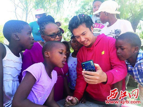 孔维聪给非洲民众看手机里的中国相片。 受访者供图