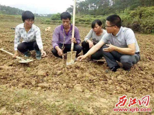 冯永成(右一)生前到田间地头向村民传授农业科技知识。 市扶贫办供图