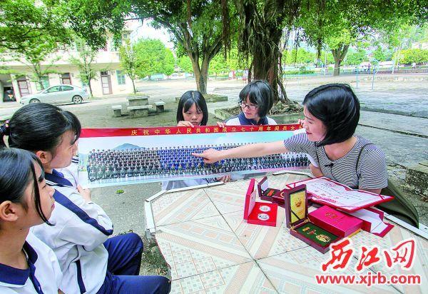 黄栎婷向学弟学妹们指出自己在阅兵女兵方队合照中的位置。 西江日报记者 曹笑 摄