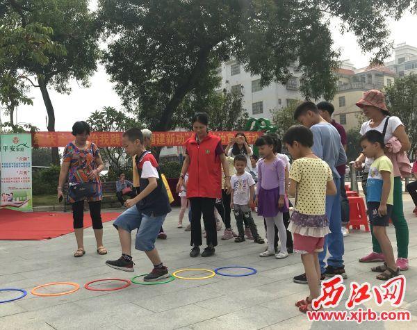 """在文峰社区,孩子们在玩""""单脚过河""""游戏,体验肢残人士的不便。西江日报记者 潘粤华 摄"""