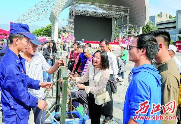 在消防员指导下,市民学习如 何专业结绳。 西江日报记者 曹笑 摄