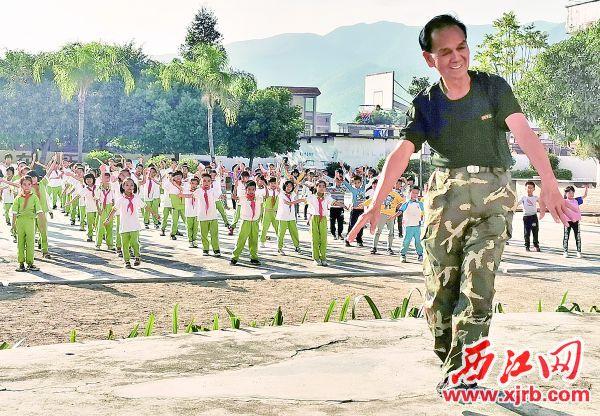 钱巍在高要大湾镇朗第小学教学生们跳《我和我的祖国》。 西江日报记者 郭巍 摄