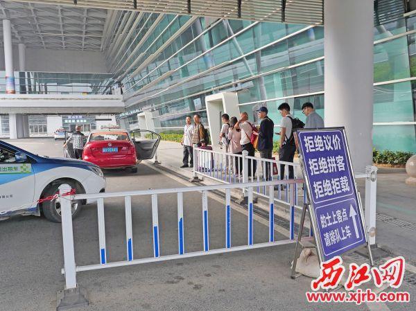 出租車排隊候客,乘客排隊上車。 西江日報記者 吳威豪 攝