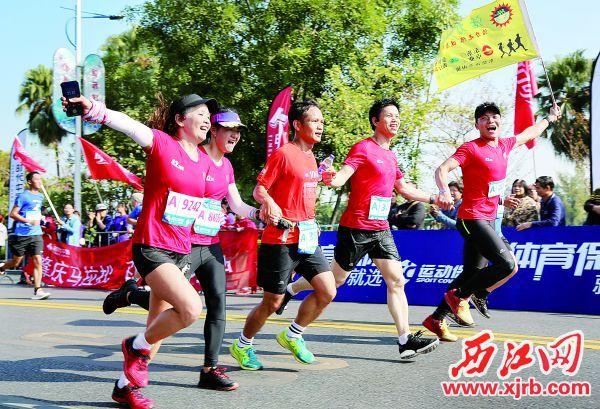 参赛选手手拉手跑向终点。 西江日报记者 梁小明 摄