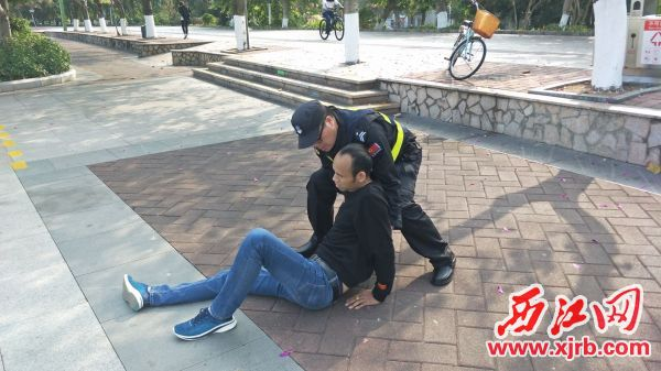 保安员李红协助伤者原地半 坐。 受访者供图
