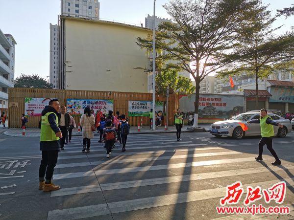 家長義工在維持交通秩序。 西江日報記者 楊麗娟 攝