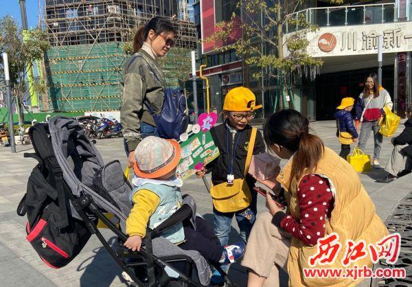 一名小孩在义卖杯子。 西江日报记者 赖小琴 摄