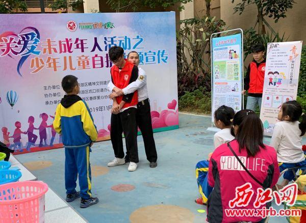 保安员向小学生演示自我保护的防护手法。 西江日报通讯员 供图